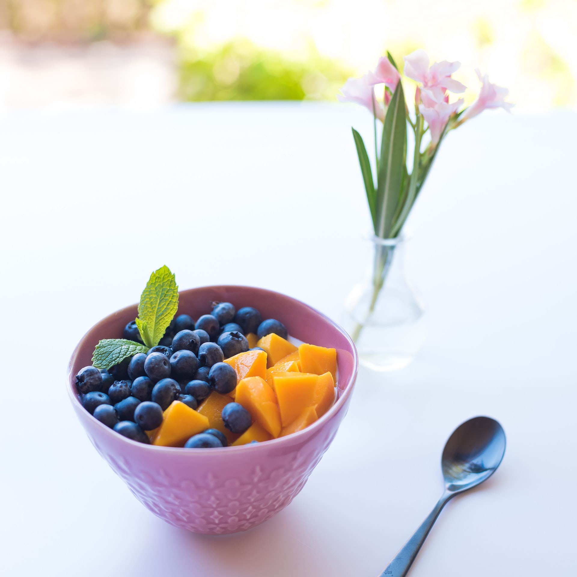 fruit bowl and flowers on a table.