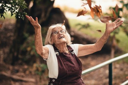 elderly woman throwing leaves