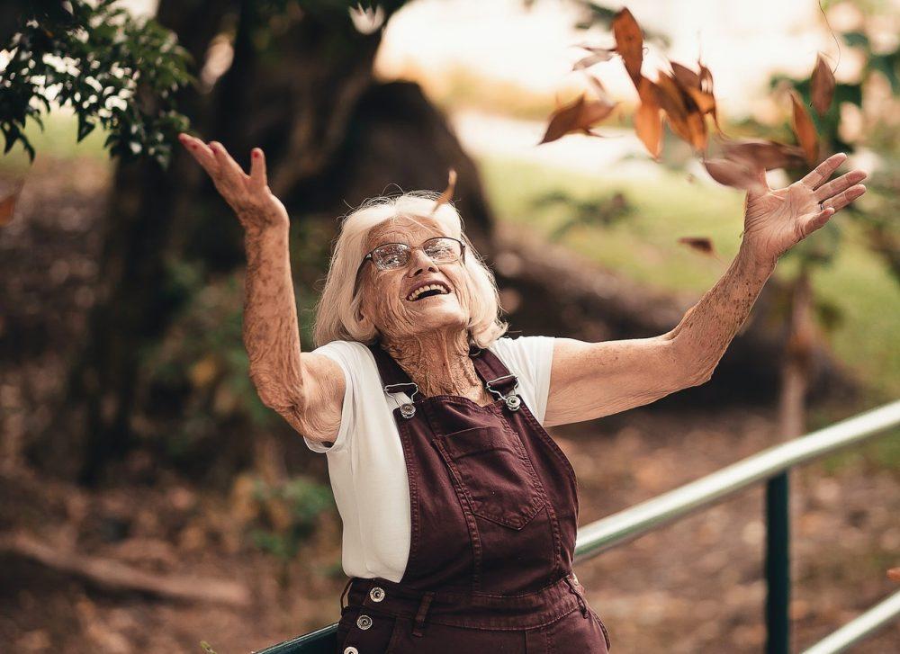 elderly woman throwing leaves