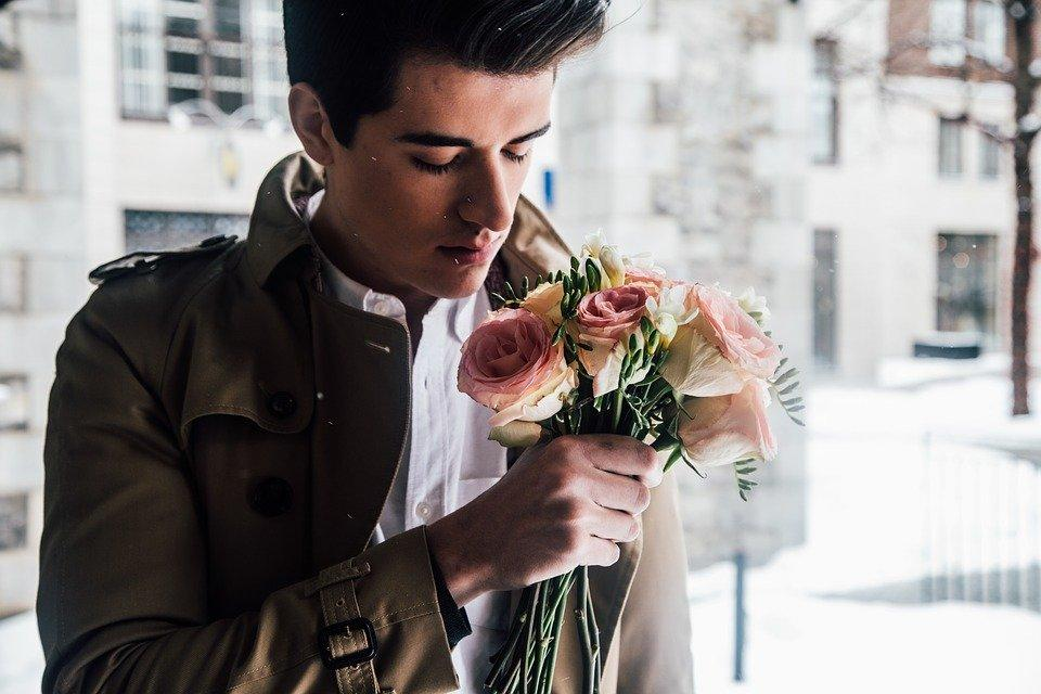 man smelling roses