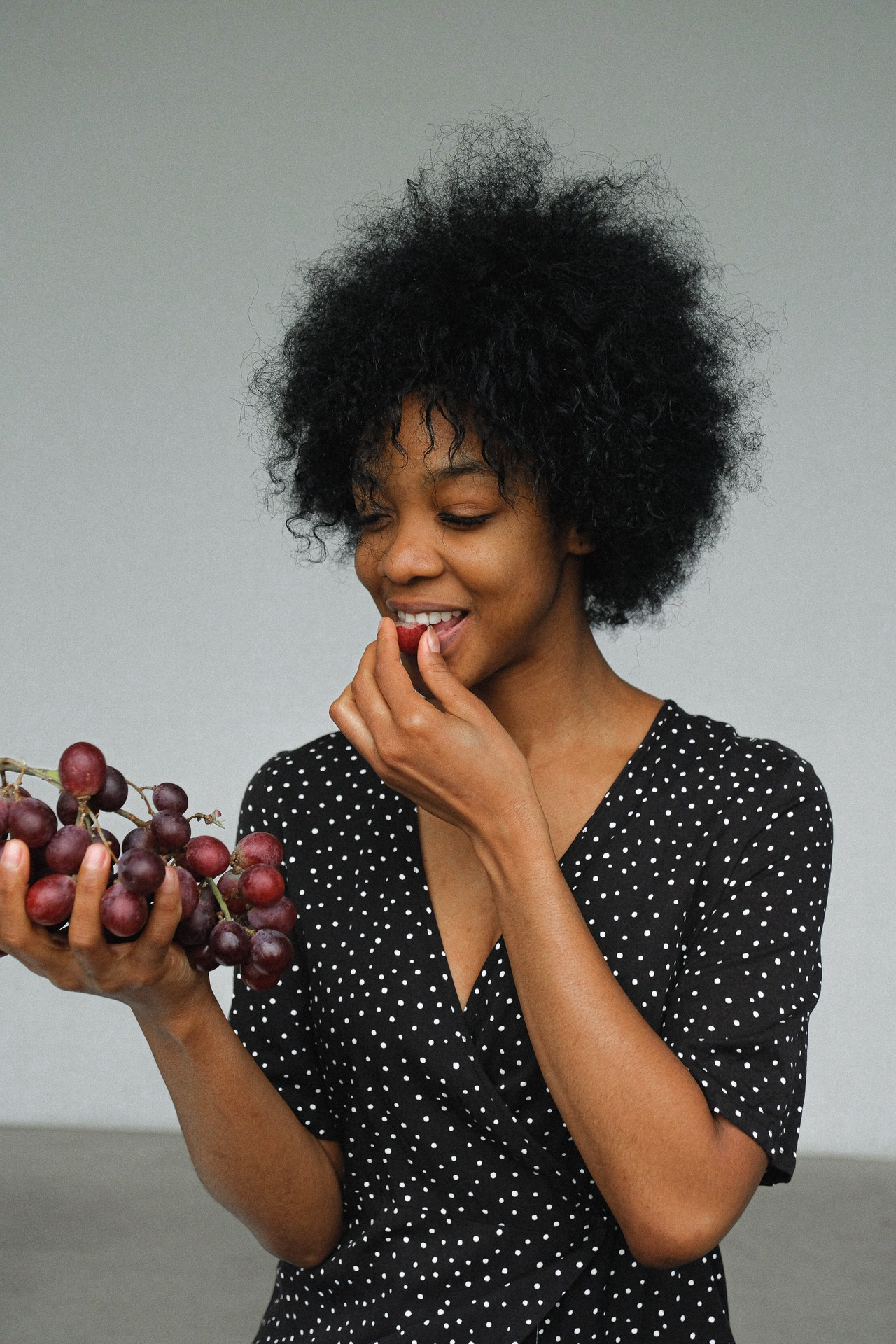 woman eating purple grapes