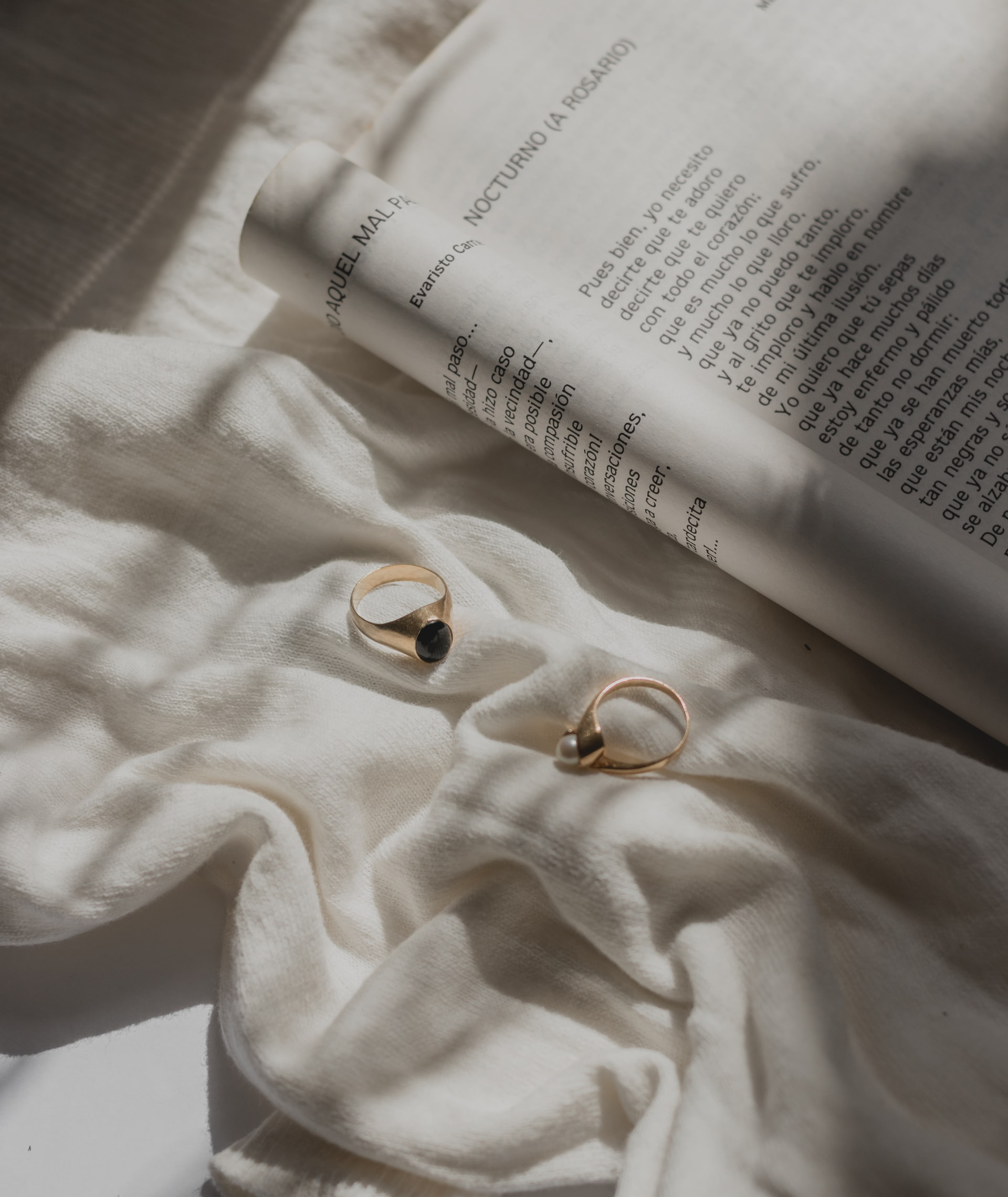 gold rings laid out on blanket next to a book