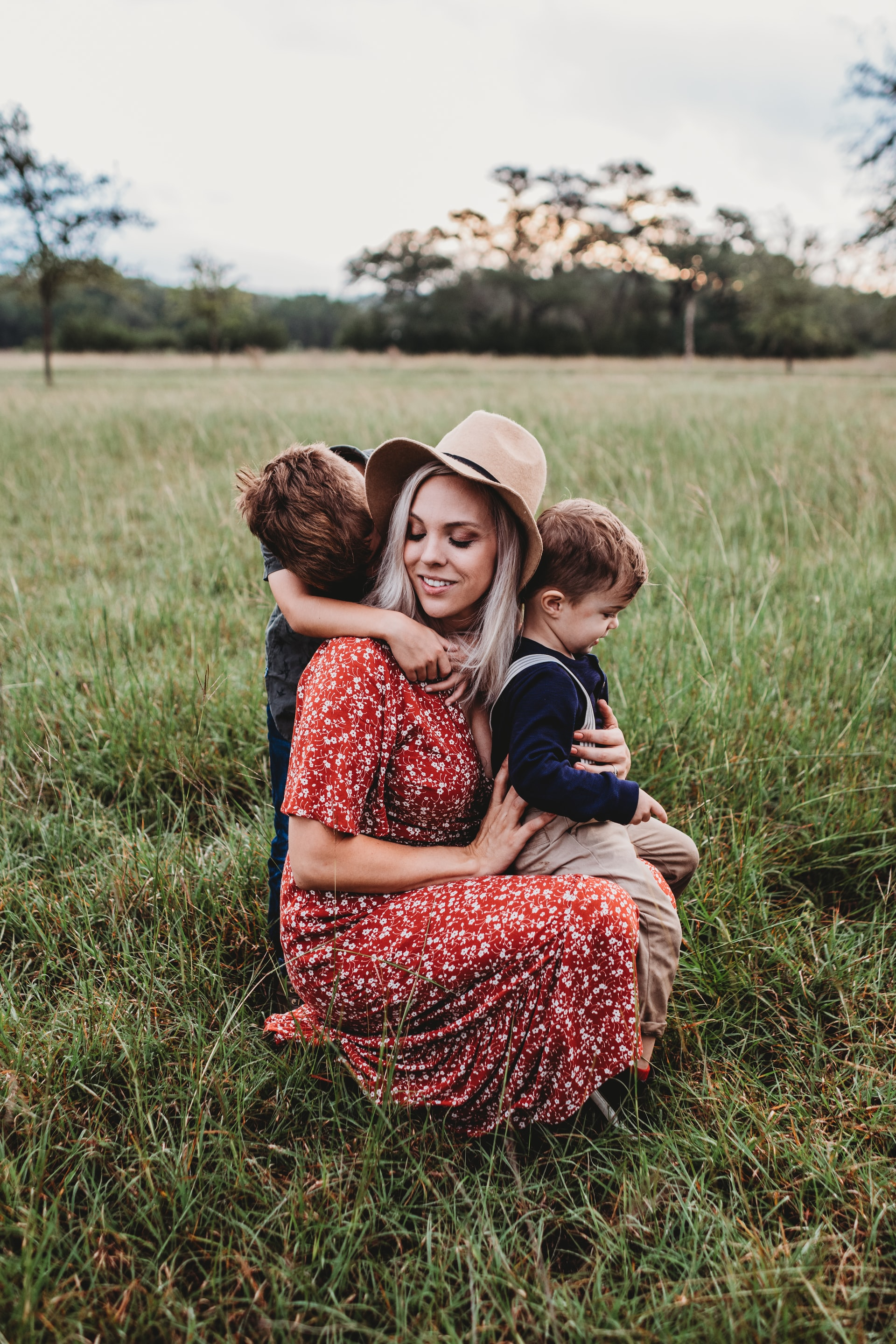 Mom in red dress with two young boys