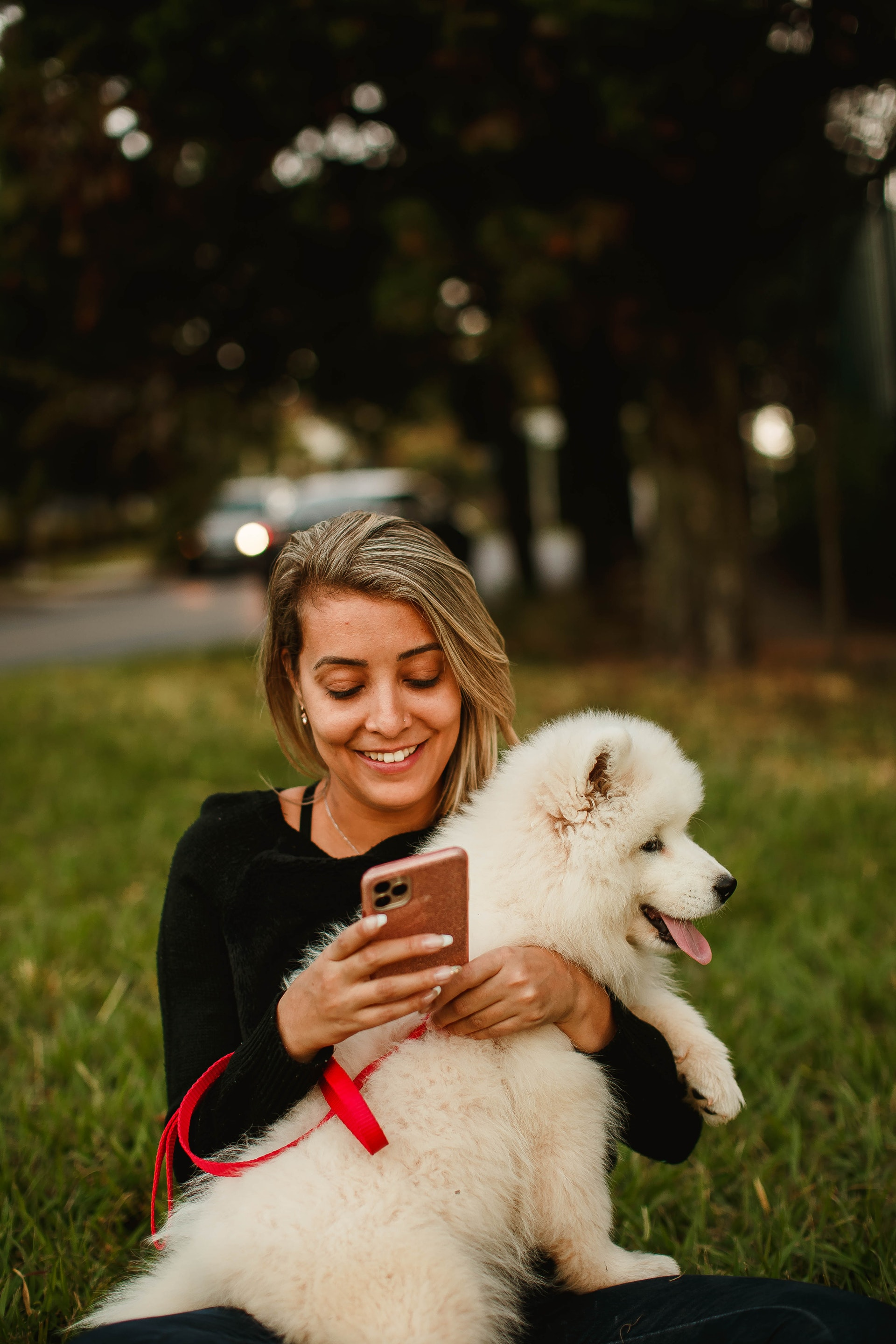 woman holding her dog in a park