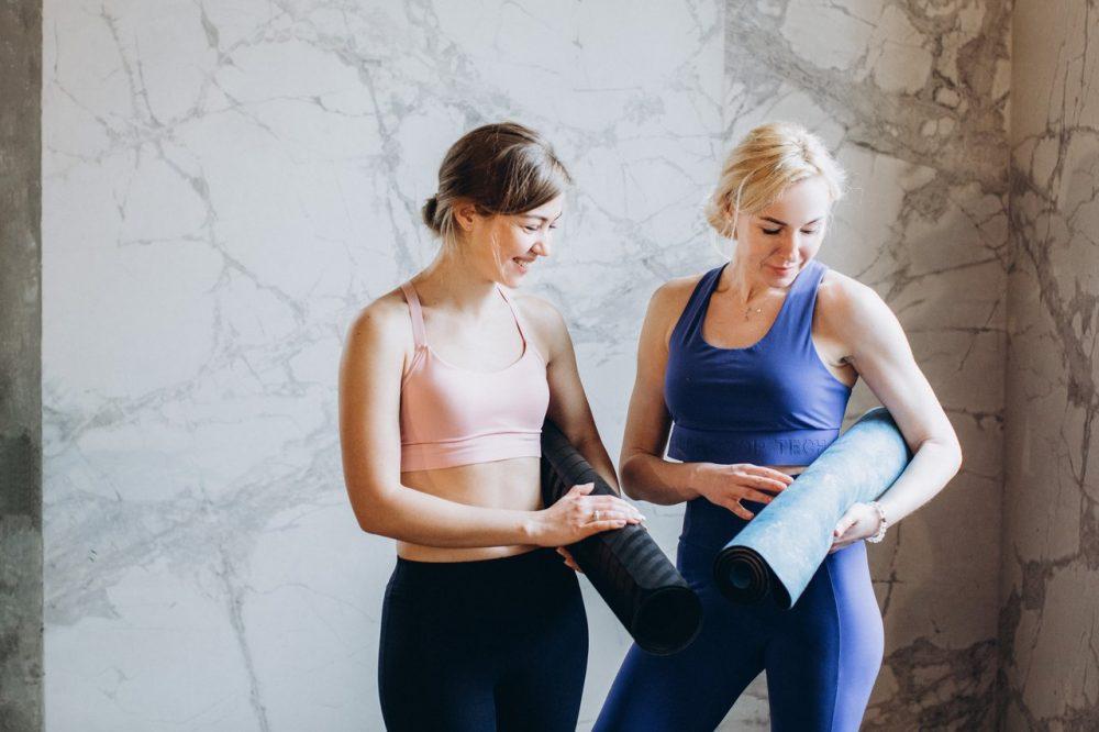 women in yoga studio holding yoga mats