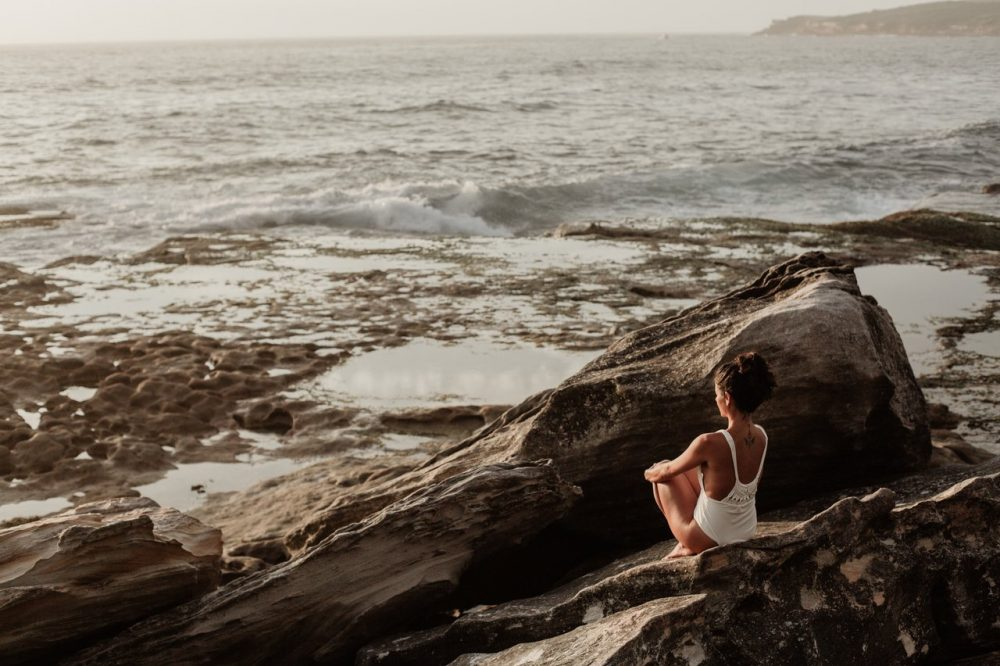 Woman sitting on rock facing ocean