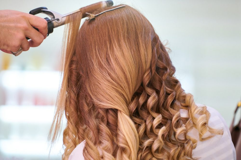 woman getting hair curled