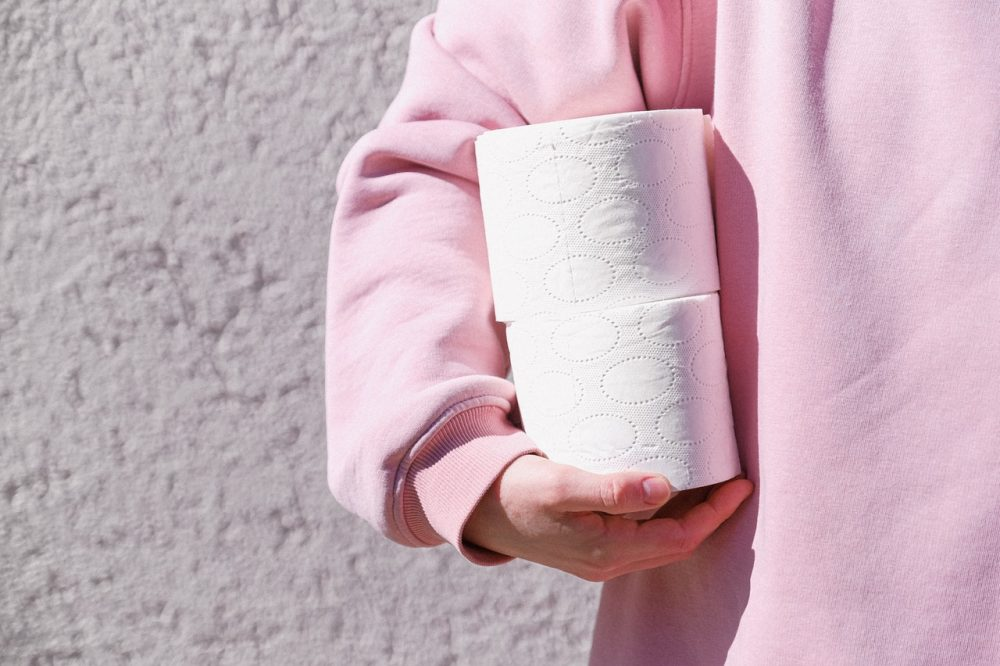 woman in pink sweatshirt holding toilet paper