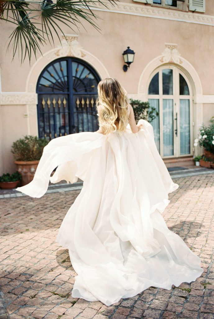 Bride spinning in wedding gown in tropical weather