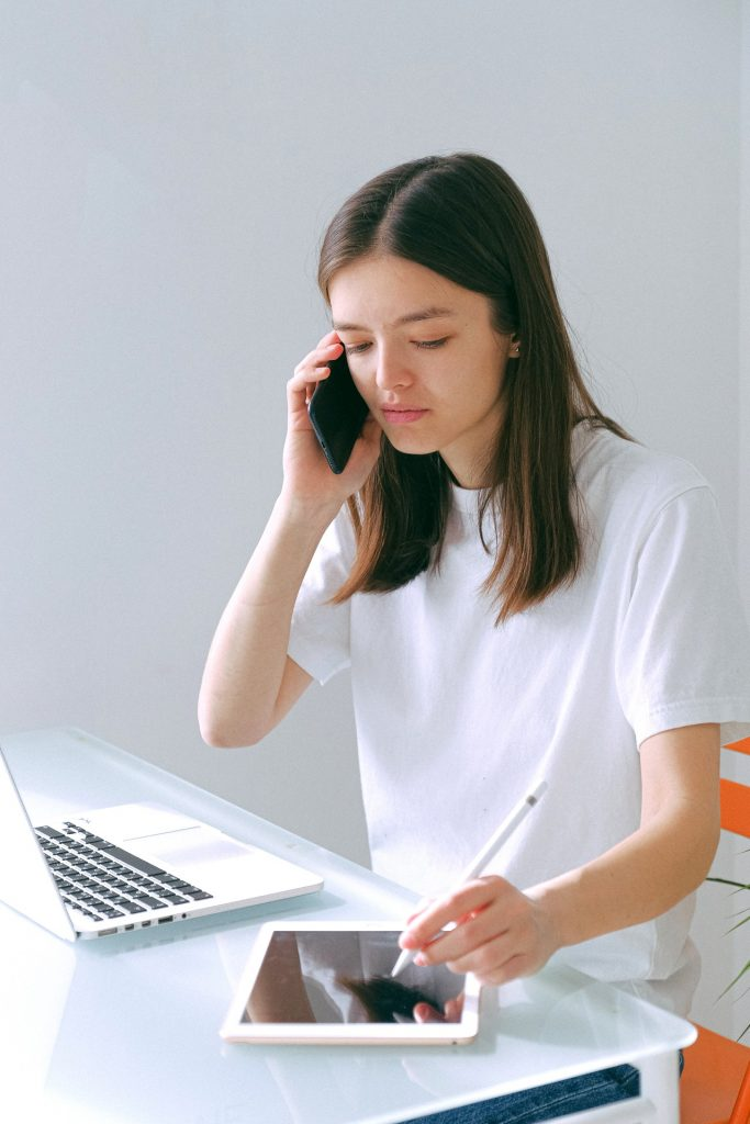 woman multitasking on phone and tablet