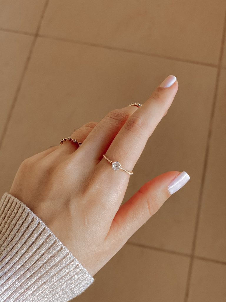 woman wearing a delicate gold solitaire diamond ring.