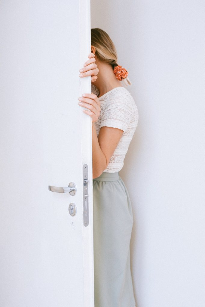 woman hiding her face with a door.