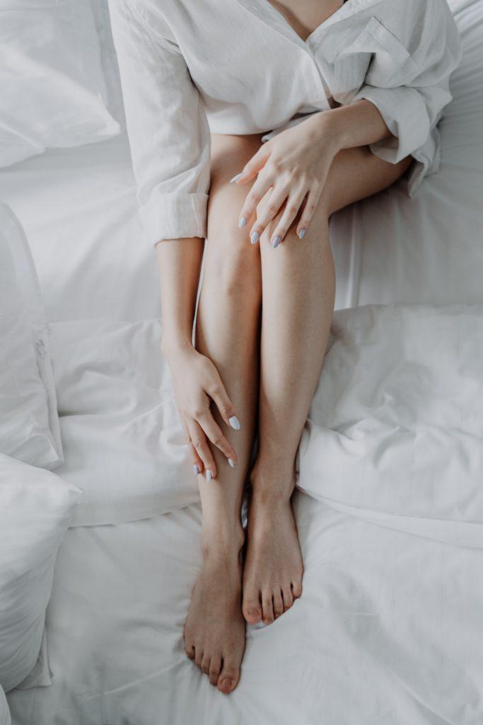 Woman with white bathrobe sitting on white bed touching legs.