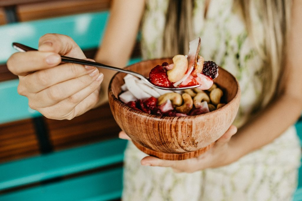 Woman eating a smoothie bowl with cashews, berries, and coconut.