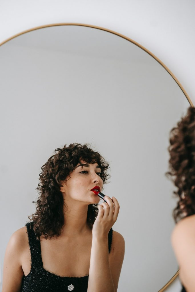 Woman with dark curly hair applying red lipstick in a round mirror.