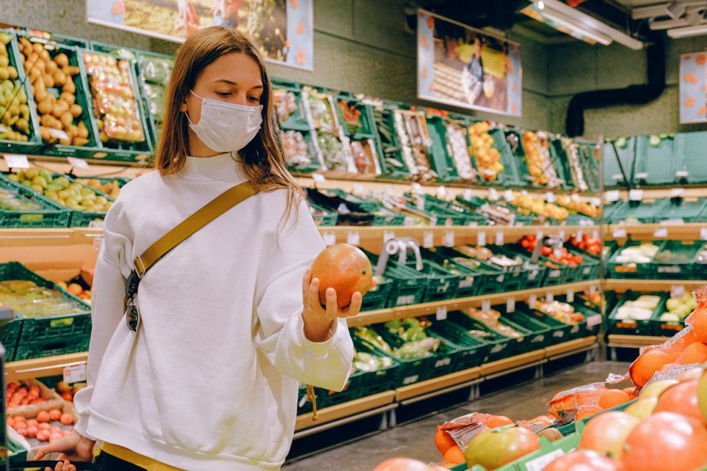 Woman grocery shopping while wearing a disposable face mask to protect herself from the covid-19 virus.