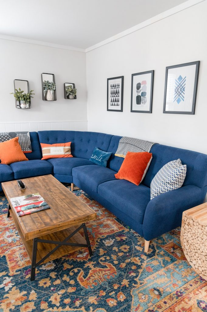Large blue fabric couch in living room with large colorful area rug.