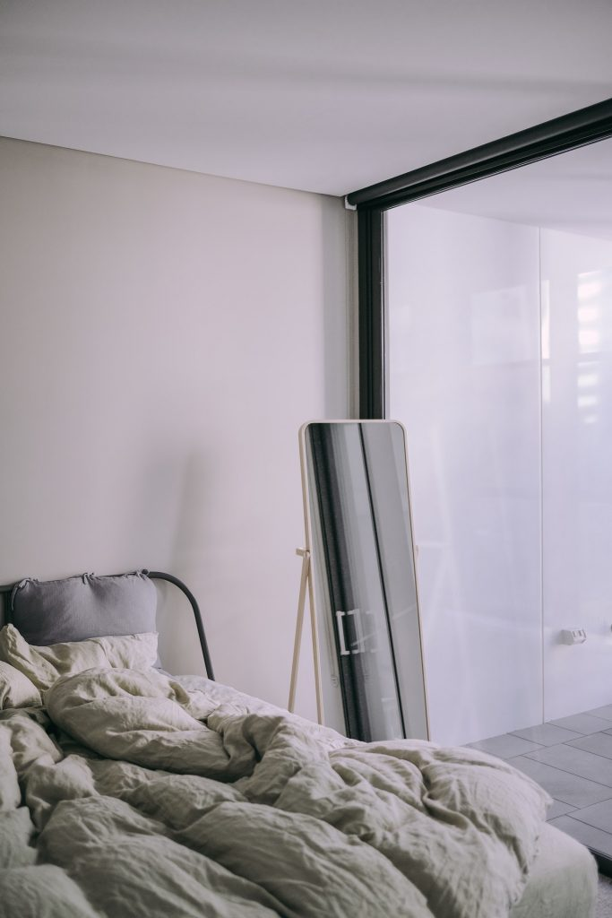 Bright and airy bedroom with an unmade bed.