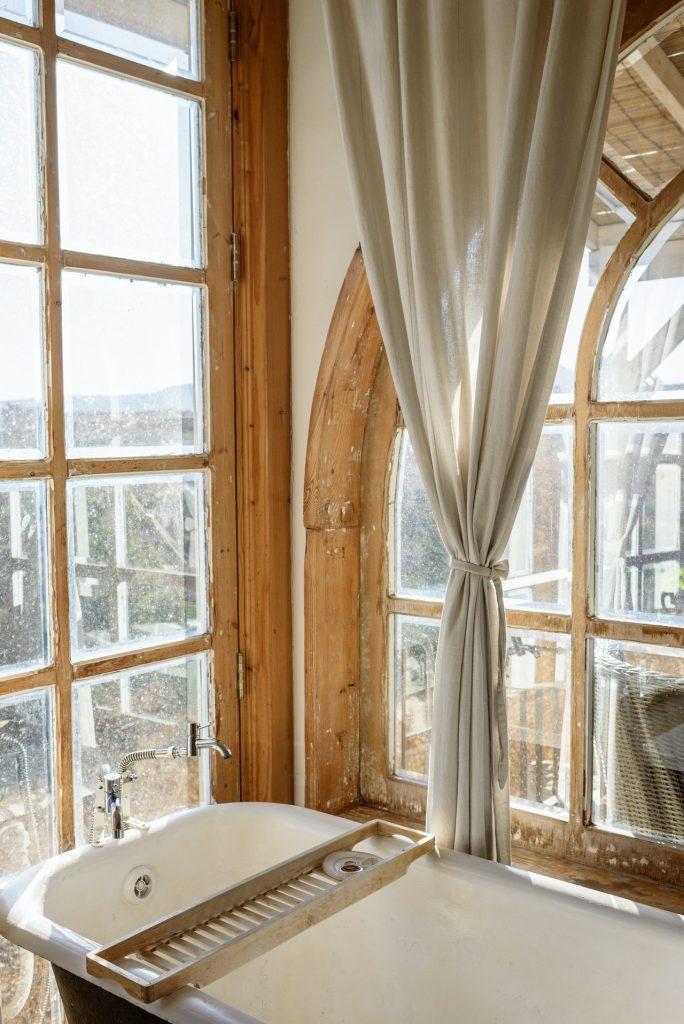 Rustic bathroom decor with large windows.