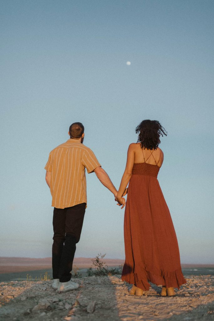 Couple looking at moon in the desert.