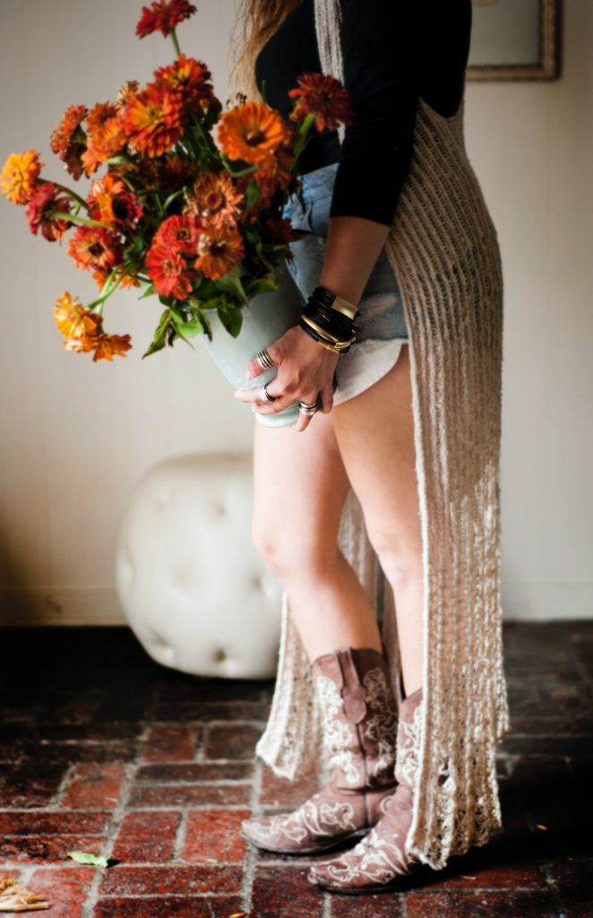 Woman holding flowers while wearing cowboy boots.