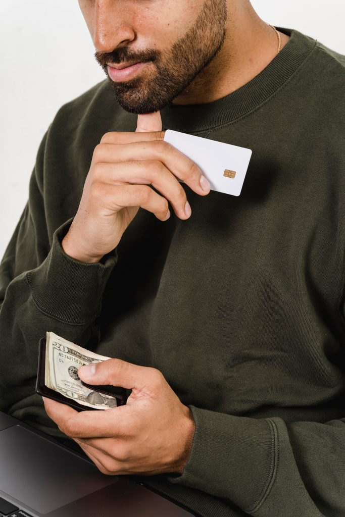 Man holding a white credit card and thinking deeply.