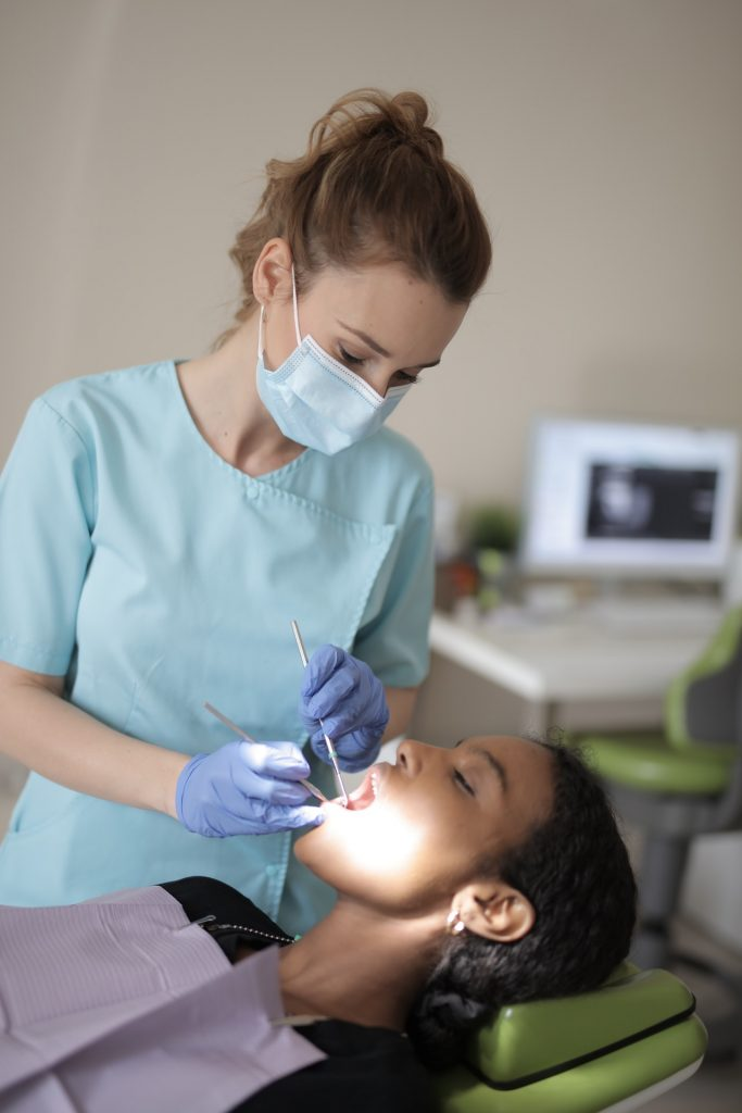 Woman getting her teeth cleaned at the dentist.