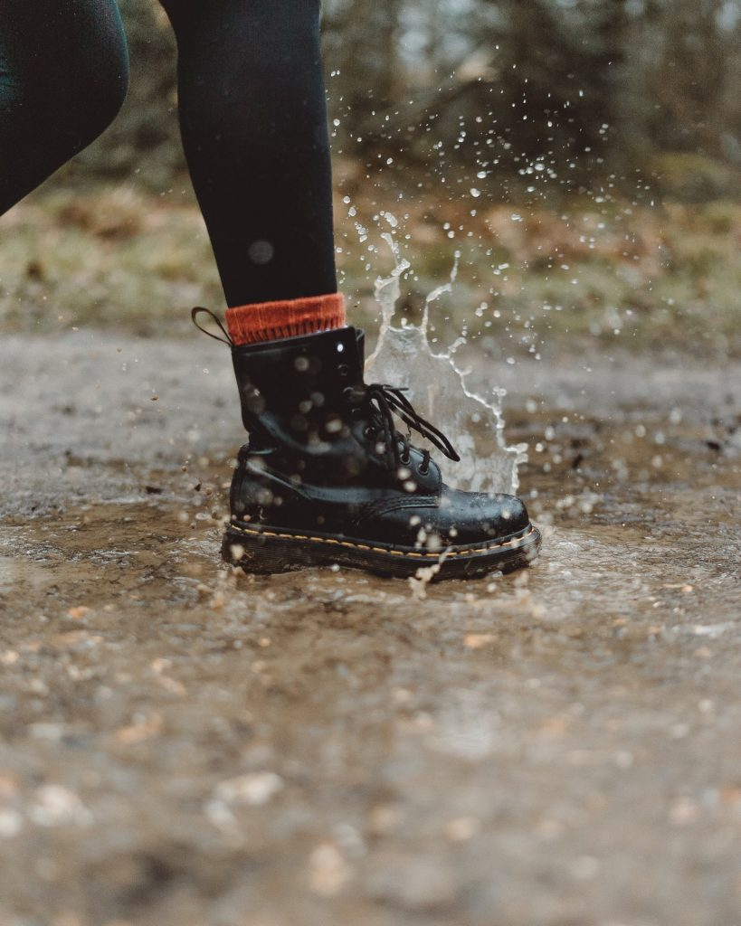 Woman stepping into a puddle while wearing Doc Martens.