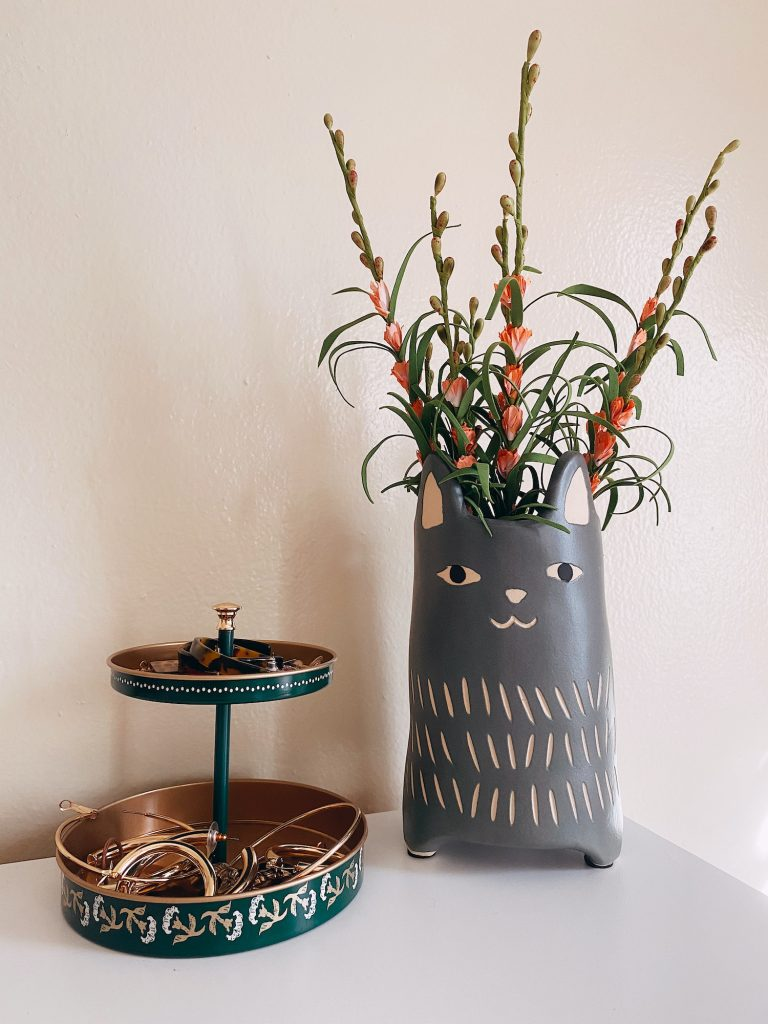 Fake flowers in a cat vase next to an IKEA jewelry holder.