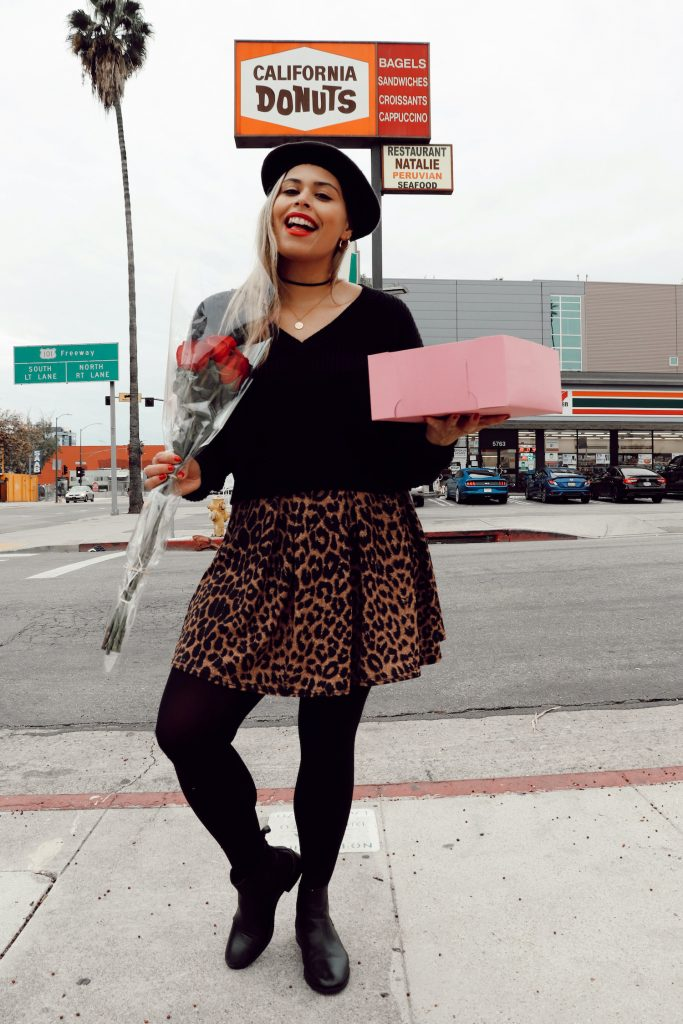 Woman wearing a baret and leopard print skirt in front of California Donut in Los Angeles.