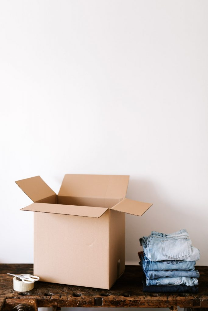 Packing jeans into a moving box.