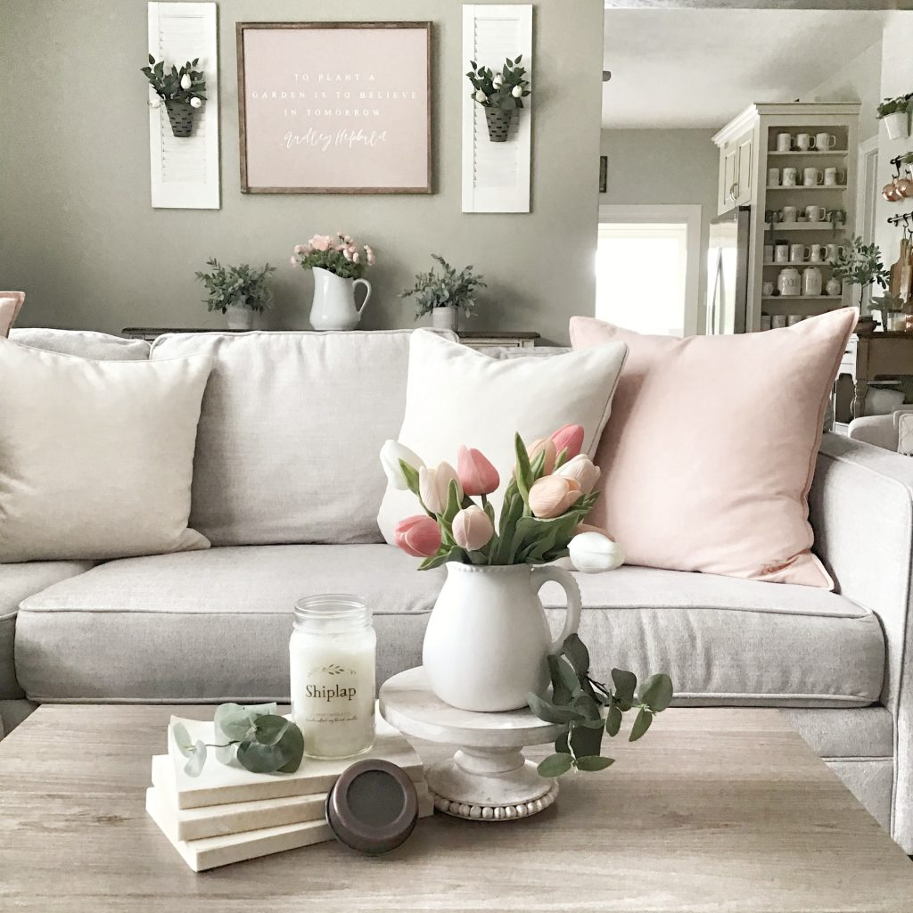 grey and pink living room decor with pink and white tulips on the coffee table.