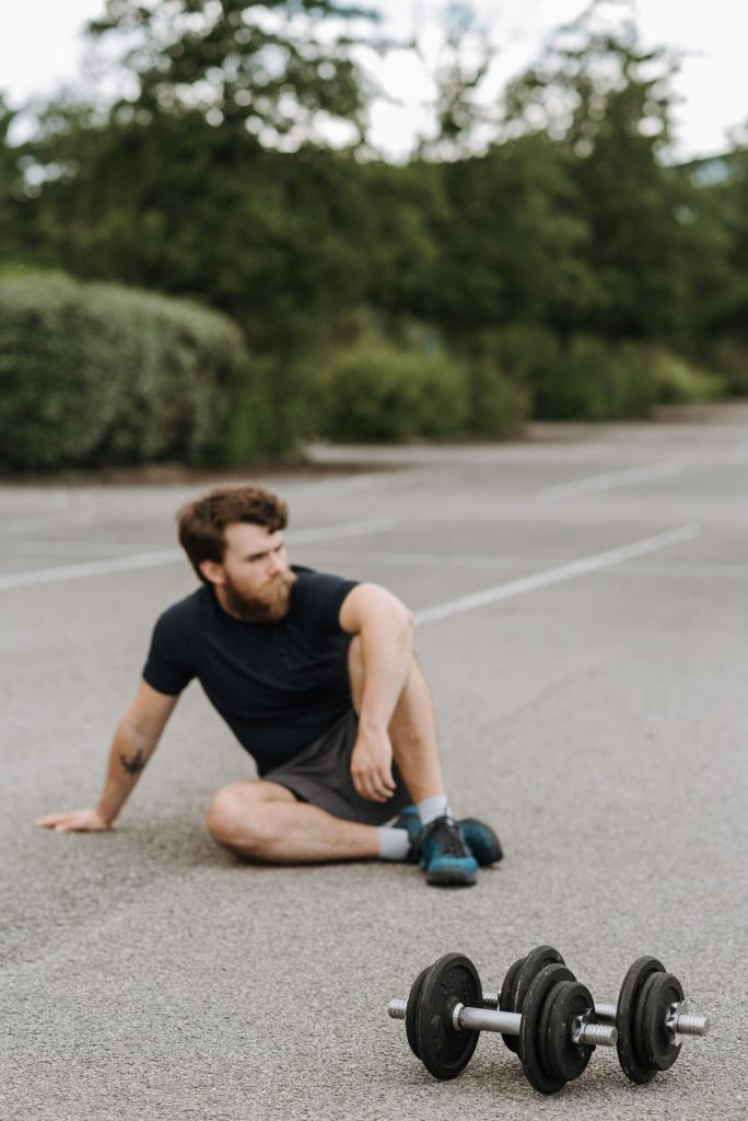 Man sitting down on ground after workout with heavy dumbbells in front of him.