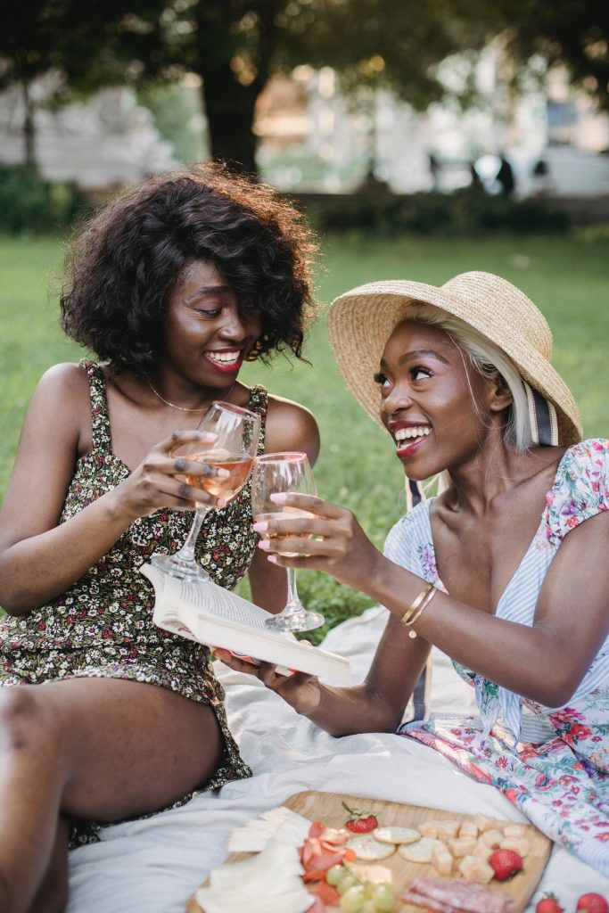 Two women in floral dresses sitting outside having a picnic with strawberries and wine.