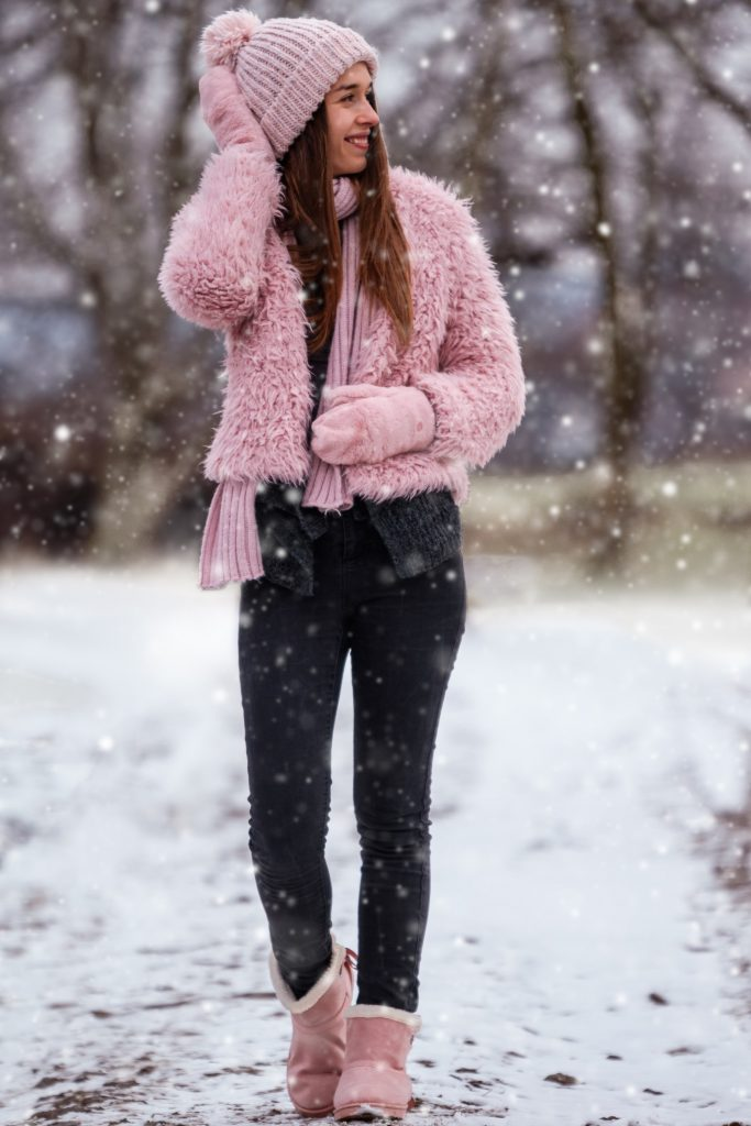 woman walking in snow wearing pink ugg boots.