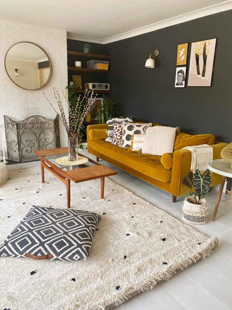 Yellow couch in a boho chic living room with a black statement wall.