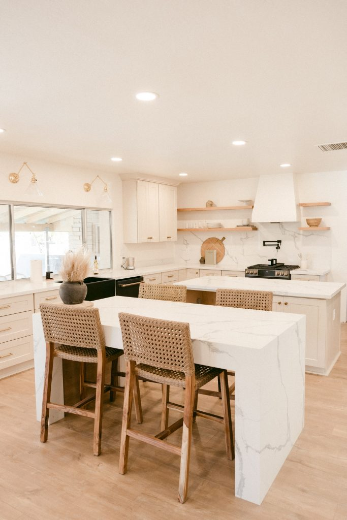 Stylish kitchen with rattan chairs, marble table, and a marble backsplash.