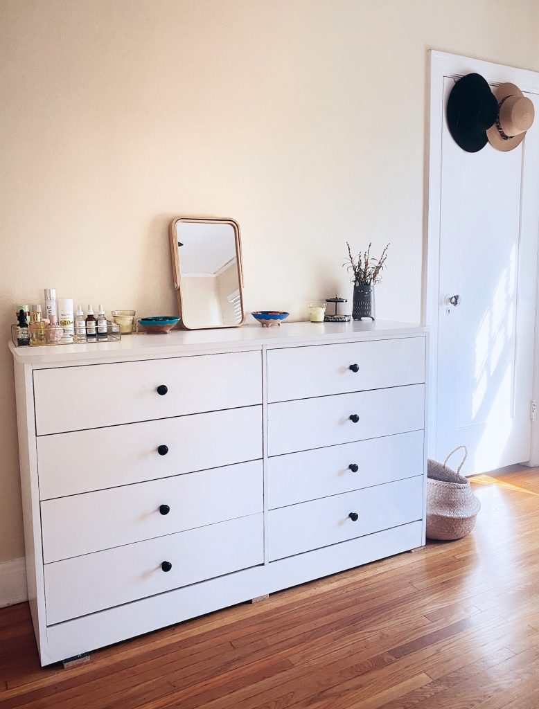 A white dresser with black knobs in a bedroom with natural light shining through.