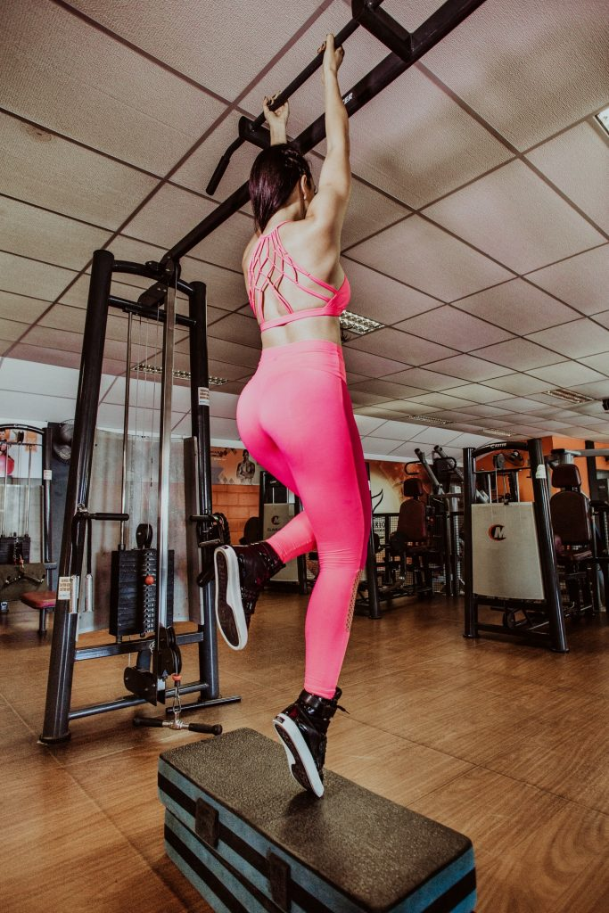 Woman in hot pink sports bra and leggings doing pull-ups in a gym.