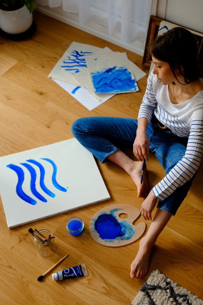 Woman sitting on floor painting with blue acrylic paint.