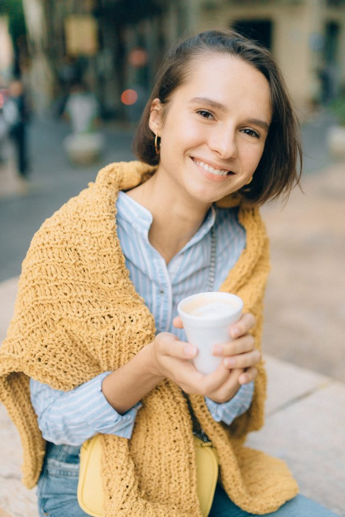Woman with yellow sweater over shoulders sitting on bench smiling while holding a topless coffee cup.