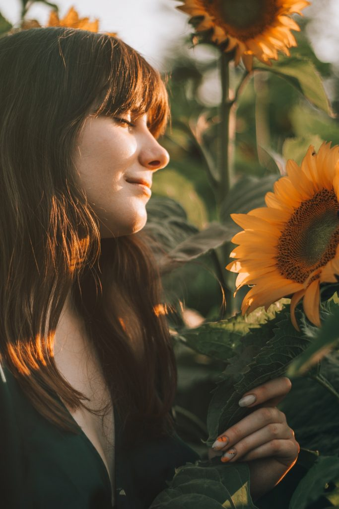 Woman with brown hair and bangs with eyes closed smelling sunflowers during golden hour.