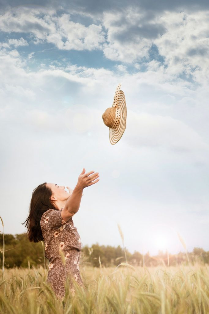 Woman standing in field throwing a straw hat in the air.
