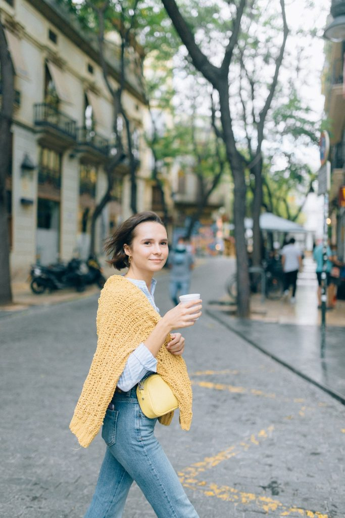 woman with yellow sweater and jeans walking in a city holding a cup of espresso.