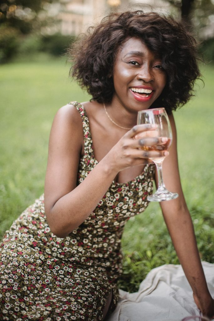 Woman in floral dress drinking wine outside on a blanket.