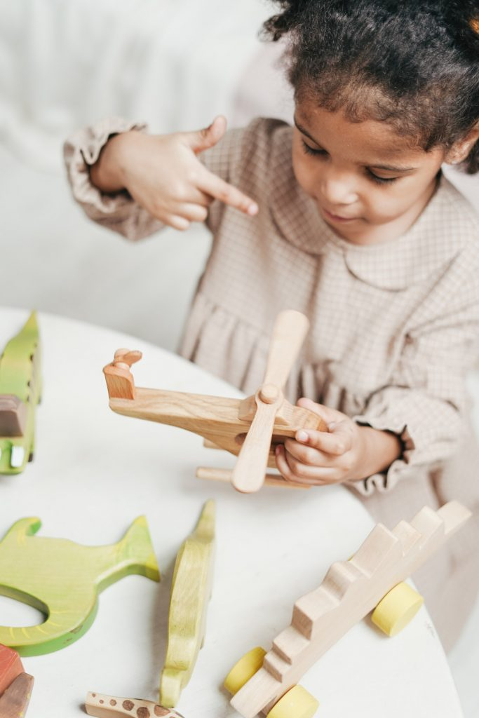 Child playing with a wooden airplane in a preschool setting.
