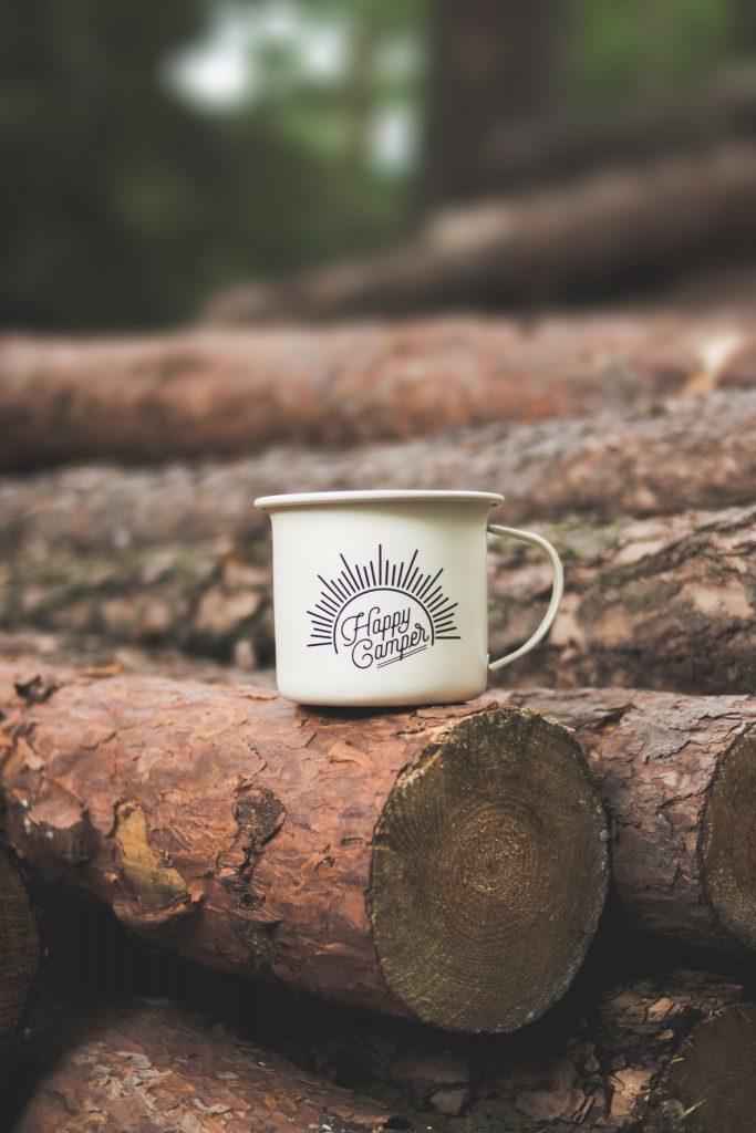 Happy Camper mug on log outside.