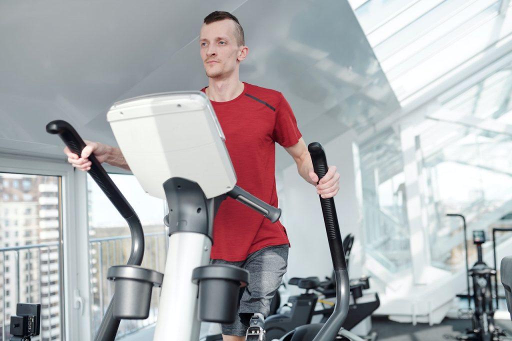 Man wearing a red shirt using an elliptical machine at a gym.
