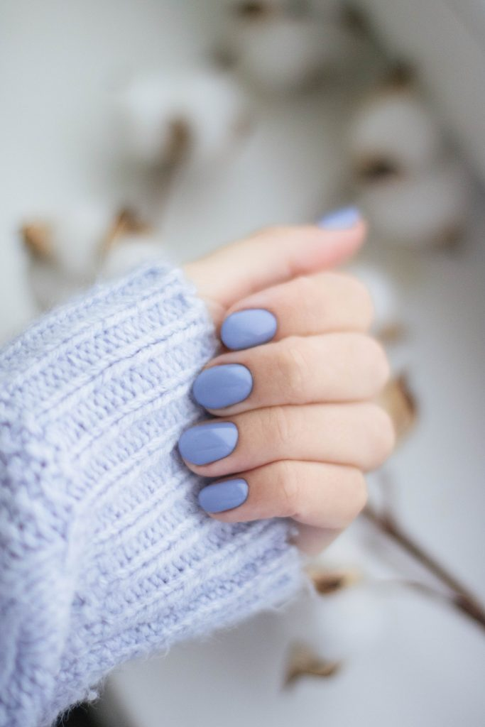 Woman's hand with periwinkle blue nail polish.