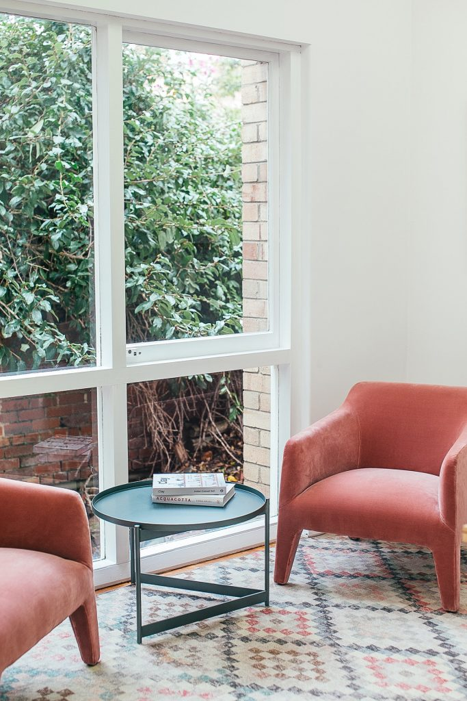 Pink velvet chairs in front of a large window.